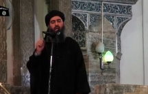 Abu Bakr al-Baghdadi is shown in a black shawl and turbine speaking into a microphone.