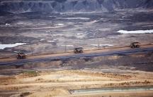 Three dump trucks in a barren landscape