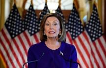 Nancy Pelosi in blue in front of American flags