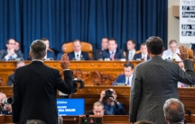 Two men stand with their backs to the camera, their right hands held in the air for an oath. Ahead of them is a row of lawmakers seated behind a large desk.