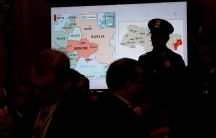 A map of Ukraine is projected onto a screen; a man in a uniform wearing a hat is silhouetted against it.