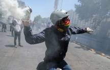 A protester with a bandana covering their face and wearing a helmet, cocks an arm back to throw a smoking canister of tear gas back at police.
