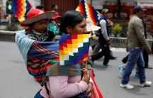 An indigenous woman holding a Wiphala flag carries a kid, in La Paz, Bolivia November 13, 2019.