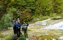 Four men stand outside in a valley near a river bed