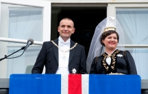 Man and woman wearing crown stand on balcony with blue, white and red flag in front of them