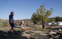 Children play with a wheelbarrow.