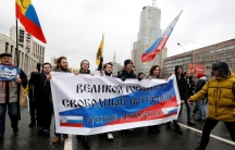 """People walk with a banner that reads: """"GreatRussia, Freeinternet""""."""