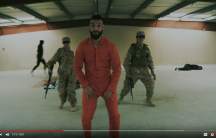 Man in orang jumpsuit dancing in front of two people in army fatigues