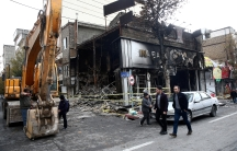 Iranians walk past a burned and destroyed bank.