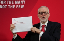 Britain's opposition Labour Party leader Jeremy Corbyn is shown holding a white piece of paper off to his side with red lettering.