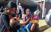 Two women sit on the curb with their infants as doctors and nurses strike at local hospital