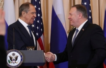 Two white men in suits shake hands, the US State Department podium is visible.
