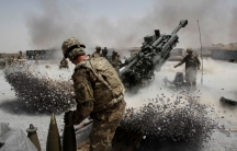 US Army soldier is show firing a howitzer weapon, the exhaust of which has made piles of rocks fly on opposite sides of the artillary.