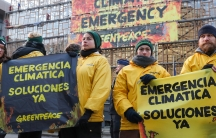 Protesters wear yellow jackets and sign that speak of climate emergency in Spanish language