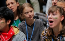 Young climate change activists sit with activist Greta Thunberg in a huddle at the climate talks in Madrid.