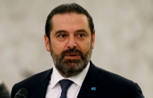 Lebanon's caretaker Prime Minister Saad al-Hariri is shown in a close-up photo standing behind a microphone and wearing a dark suit.