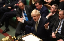 Britain's Prime Minister Boris Johnson is shown standing at a lecturn with a microphone and several parliamentary members sitting behind him.