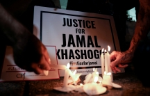"""Several white candles are burning in front of a sign that reads, """"Justice for Jamal Khashoggi."""""""
