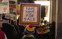 """A protester stands with a sign reading """"NHS NOT FOR SALE"""""""
