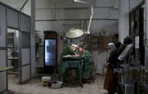 Doctors operate under a dim light in a clinic.