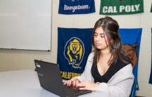 A young woman sits in front of a laptop typing.
