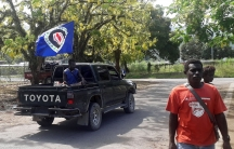 A truck carrying a Bougainville flag drives by a man.