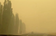A car is shown in the distance driving on a road and entirely surrounded by dark yellow smoke.