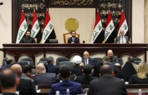 Three leaders of Iraq's paliament are shown sitting at the front of a large room with other lawmakers.
