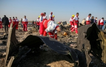 Dozens of workers dressed in red and white overalls are shown at an airplane crash site.