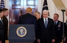 President Donald Trump departs from a podium, flanked by several officials