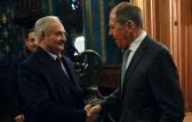 Khalifa Haftar and Russian Foreign Minister Sergei Lavrov, both wearing suits, are shown shaking hands.