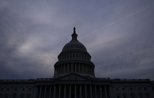 A dark blue sky is shown at sunset behind the dome of the US Captiol building in shadown.