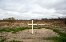 A single white cross is shown on a small dirt area amongst a wide open grassy field.