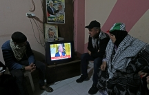 Palestinians watch a television broadcasting the announcement of Middle East peace plan by US President Donald Trump, in the southern Gaza Strip on Jan. 28, 2020.