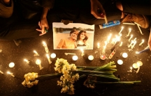 Candles surround a photo of a woman and girl.