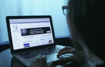 A woman uses Wikipedia on a laptop.