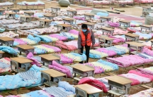 A worker amid a room of cots