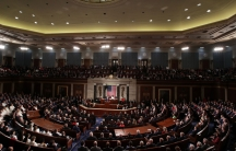 US President Donald Trump is shown standing at a podium at the center of a joint session of Congress.