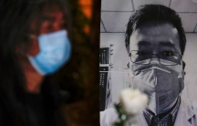 A person wearing a mask is shown in soft focu near a black and white photograph of Dr. Li Wenliang.