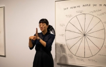 """Christine Sun Kim is shown signing and standing in front of her art featuring a pie chart titled """"Shit Hearing People Say To Me."""""""