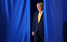 US President Donald Trump is shown walking through a parted blue current and wearing a suit.