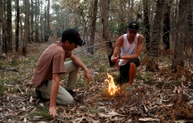 Two men bend over a small fire in the forest