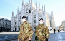 Military officers in full fatigues are shown wearing face masks and standing outside Duomo cathedral.