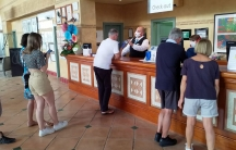 """Several people are shown standing at the counter of a hotel resort with the words, """"Check out"""" on a sign behind the counter."""