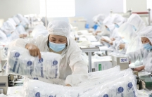 People are shown in all white medical protective gear and face masks while working on a medical supply line.