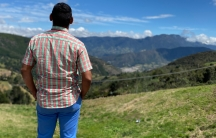 A man wears jeans and plaid shirt with back to camera facing mountain range