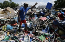 A man picks through a huge heap of plastic trash