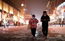 People wearing face masks walk along a street, as China is hit by an outbreak of the newcoronavirus, in Beijing,Feb.5, 2020.