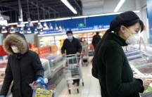 People wearing face masks look for products at a supermarket, as the country is hit by an outbreak of the new coronavirus, in Beijing,Feb. 19, 2020.