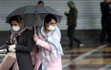 Iranian women wear protective masks to prevent contracting coronavirusas they walk in the street in Tehran,Iran, Feb.25, 2020.